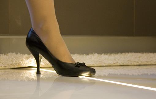 Kobieca stopa w butach na obcasach stoi na podświetlanej fudze w łazienkowej podłodze