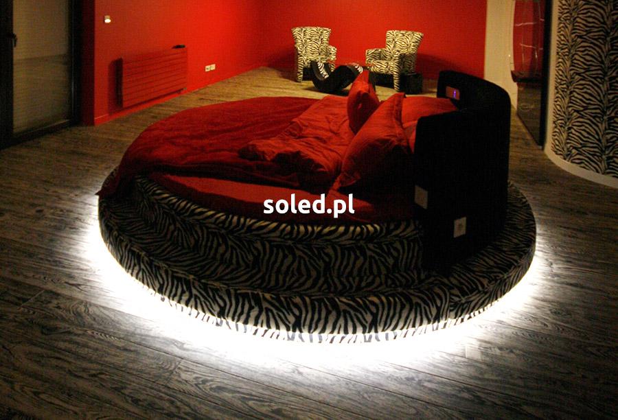 podświetlone łóżko okrągłe z czerwoną pościelą