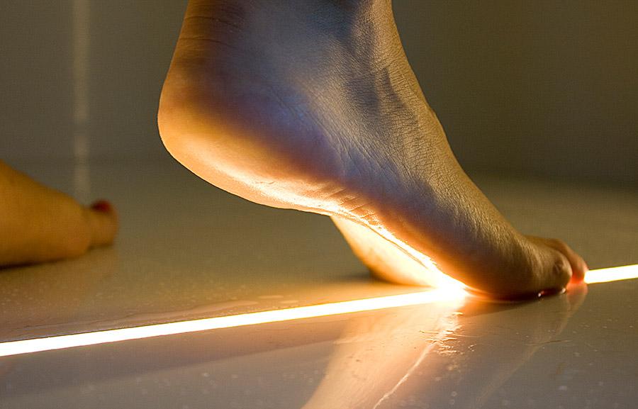 podświetlenie fug, po których stąpa nagą stopą człowiek
