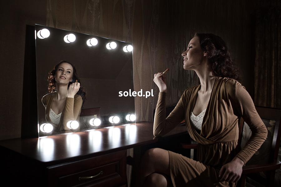 romantyczne oświetlenie sypialni to lustro do wizażu umieszczone na drewnianej toaletce, przy lustrze siedzi kobieta, która wykonuje makijaż