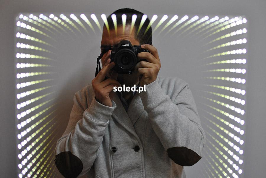 lustro 3D z efektem głębi, przed którym stoi mężczyzna robiący zdjęcie lustrzanką