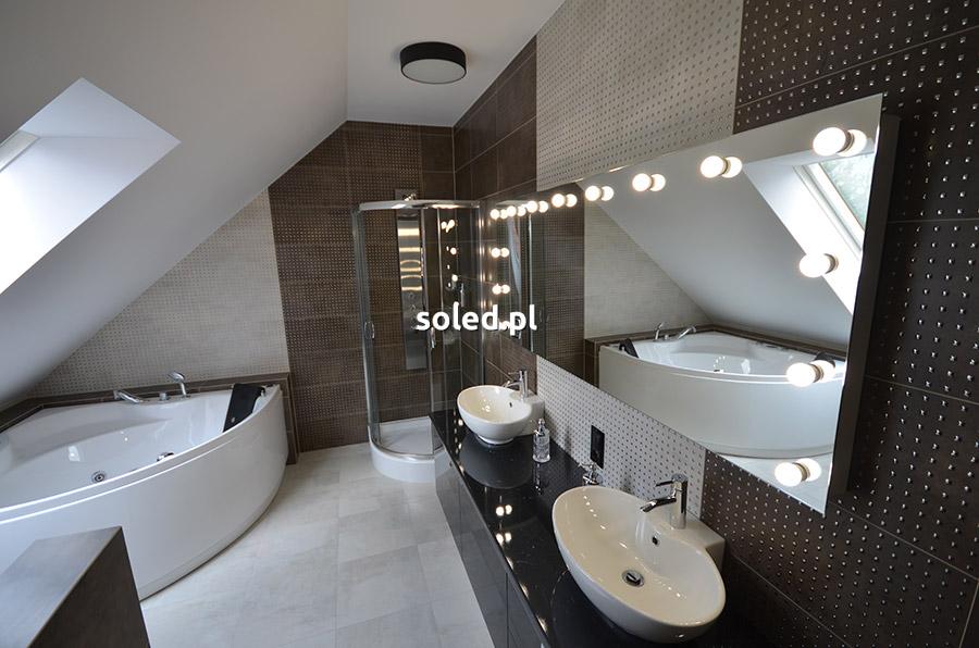 lustro z żarówkami w łazience nowoczesnej zawieszone nad zlewem, w oddali widać wannę narożną