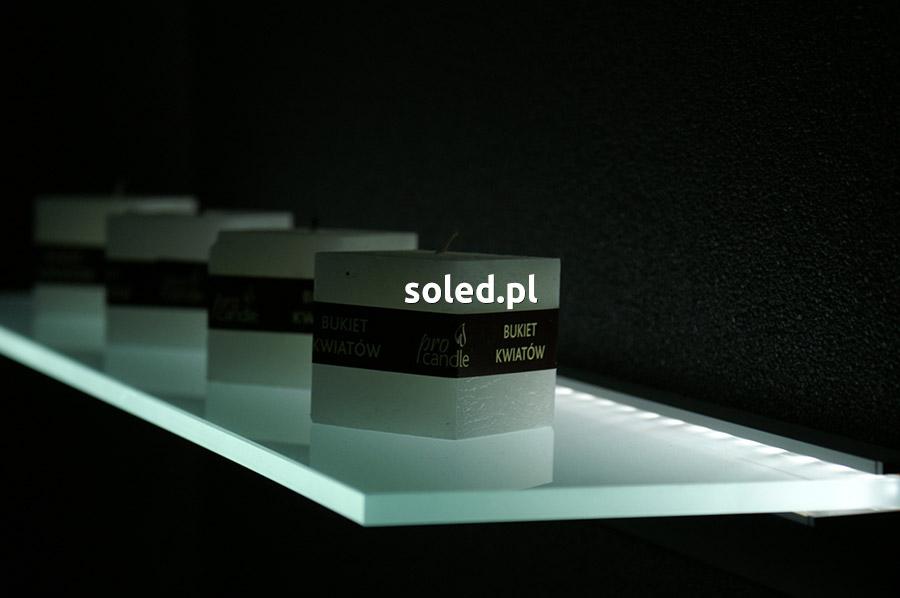 półka szklana led na ozdoby - stoją na niej świece kwadratowe