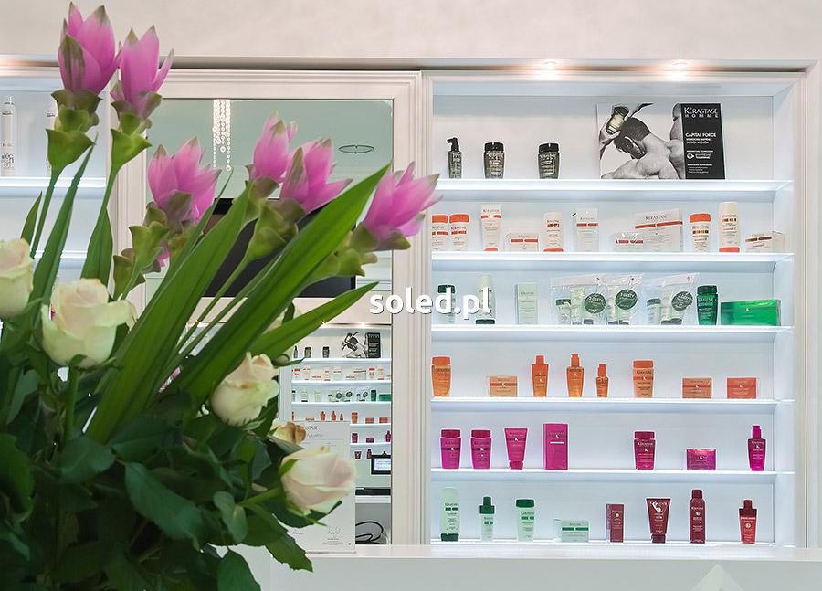 półki podświetlane led na kosmetyki - widok na półki umieszczone na ścianie, widok zza kwiatów