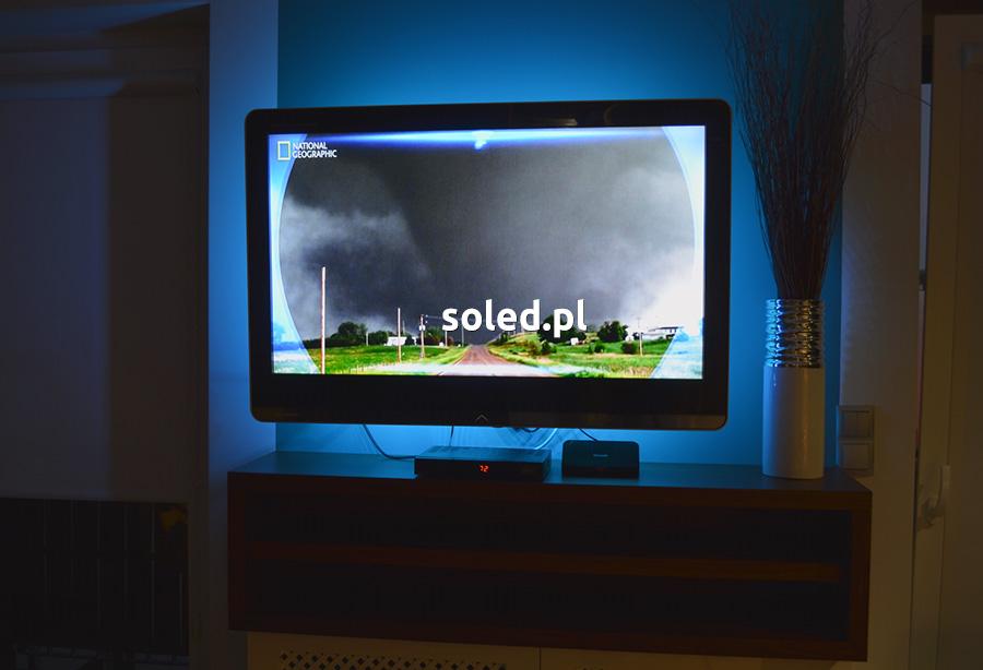 podświetlenie telewizora taśmą LED na USB, telewizor stoi na szafce w salonie i jest oświetlony niebieską łuną z tyłu