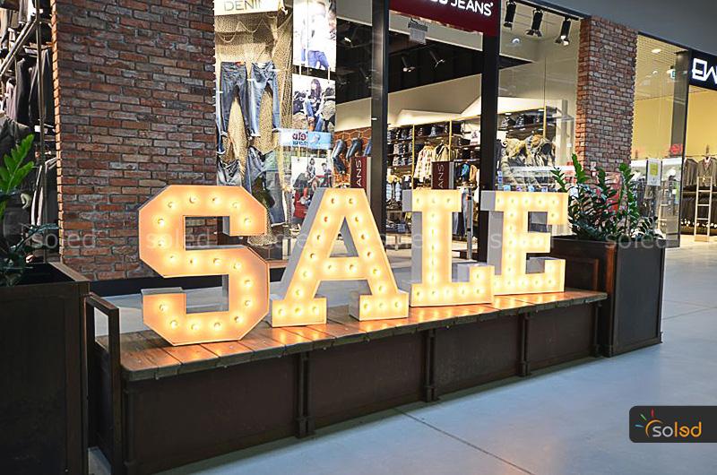 Podświetlane litery z żarówkami ułożone w napis SALE w galerii handlowej