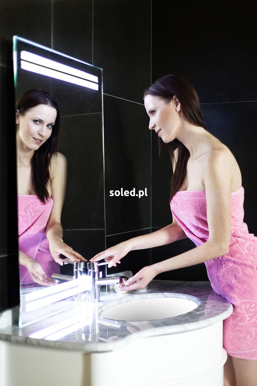 lustro LED, przed którym stoi kobieta w różowym ręczniku i próbuje odkręcić kran