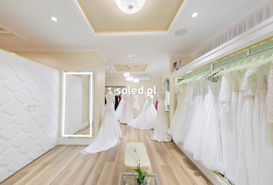 lustro LED umieszczone na ścianie w salonie ślubnym, widok na cały salon, po prawej lustro, z boku suknie ślubne zawieszone na wieszakach