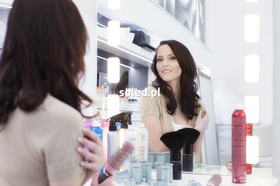 kobieta siedzi przed lustrem podświetlanym LED, w ręku trzyma przybory fryzjerskie