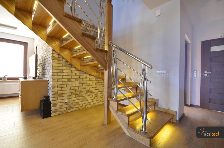 Włączone oświetlenie LED na drewnianych schodach w mieszkaniu