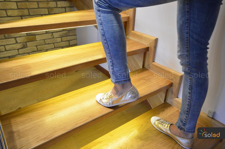 Oświetlenie schodów taśmami LED, po których idzie kobieta