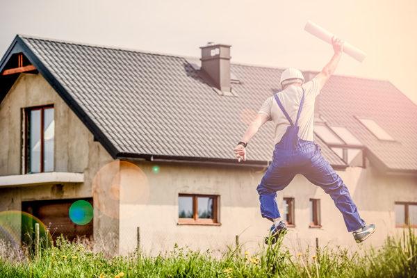 plan budowy domu w rękach podskakującego pracownika na działce obok domu