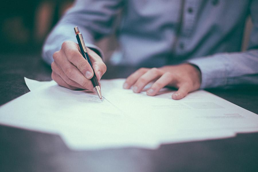 człowiek podpisuje dokumenty