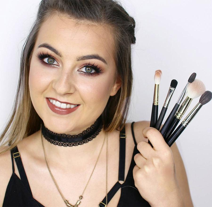Zdjęcie vlogerki lamakeupebella z pędzlami do makijażu trzymanymi w dłoni