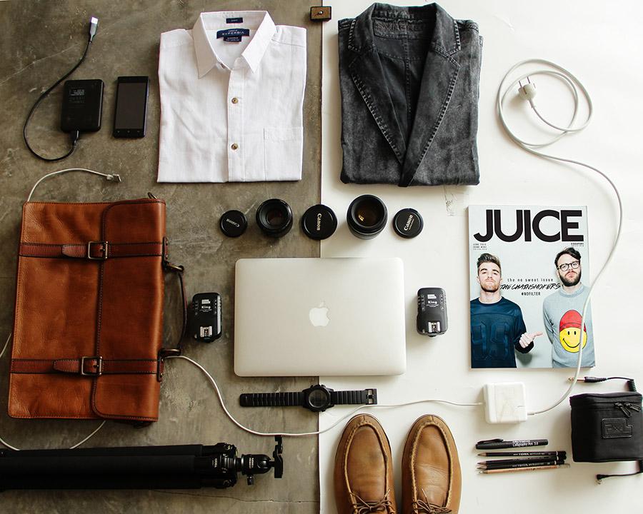 Różne przedmioty do spakowania leżące na podłodze np. laptop, torba, koszule, buty, telefony, długopisy