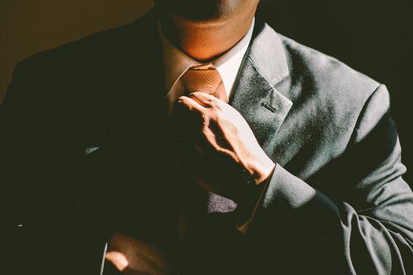 mężczyzna w garniturze poprawia krawat