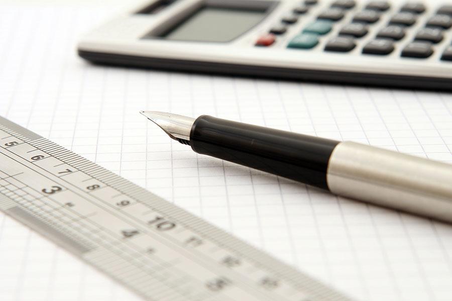 kalkulator, linijka i długopis na tle kartki