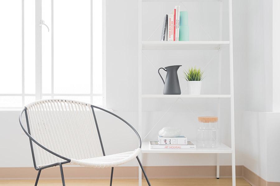 nowoczesny biały salon z oknem, a w nim widoczne designerskie krzesło i minimalistyczny biały regał z kilkoma książkami, dzbankiem i doniczką z zieloną rośliną