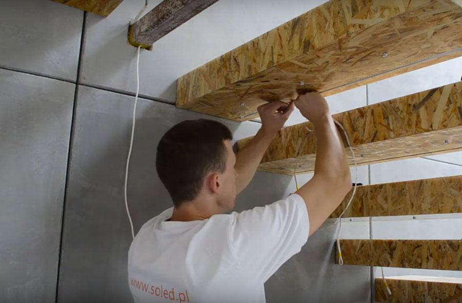 pracownik SOLED zajmuje się montażem taśmy LED na schodach z płyty OSB