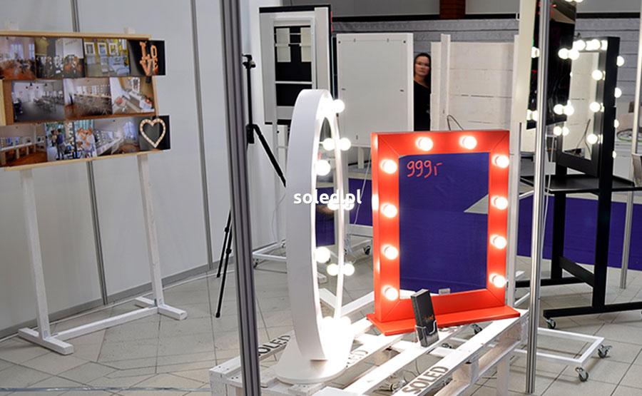stoisko SOLED z lustrami stojącymi na stoliku z palet oraz tablicą korkową ze zdjęciami z realizacji klientów