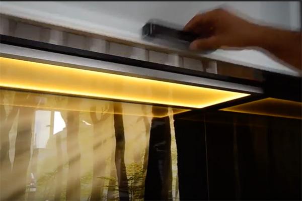 wieniec kuchenny, który służy do oświetlenia blatu w kuchni i szafek wewnątrz zbudowany ze szkła i zamontowany pod górną szafką kuchenną, na fotografii szafka otwierana jest przez mężczyzną - widać tylko jego dłoń i zbliżenie na wieniec świetlny pod szafką