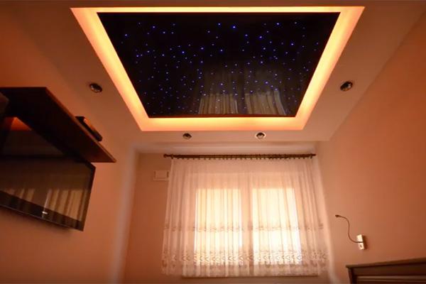 Niebo z gwiazdami na suficie w sypialni utworzone za pomocą panelu ze światłowodami, który jest zawieszony nad łóżkiem w sypialni i dodatkowo podświetlony taśmą LED po obwodzie, co daje efekt świetlnej łuny, na zdjęciu widać sufit z gwiezdnym panelem, okno, a po prawej ścianę z telewizorem