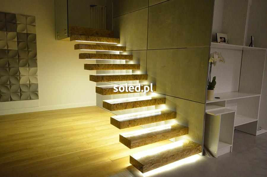 nowocesne oświetlenie schodów LED w domu, stopnie wykonane z płyt osb zamontowane z jednej strony ściany, nie posiadają barierki i wyglądają jak zawieszone w powietrzu