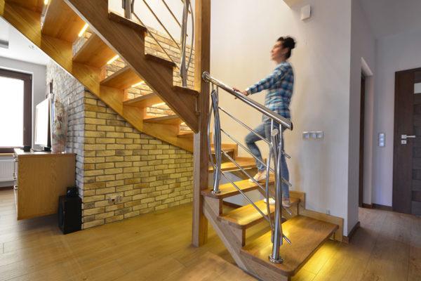 kobieta wschodzi po schodach na których zostało zamontowane oświetlenie LED