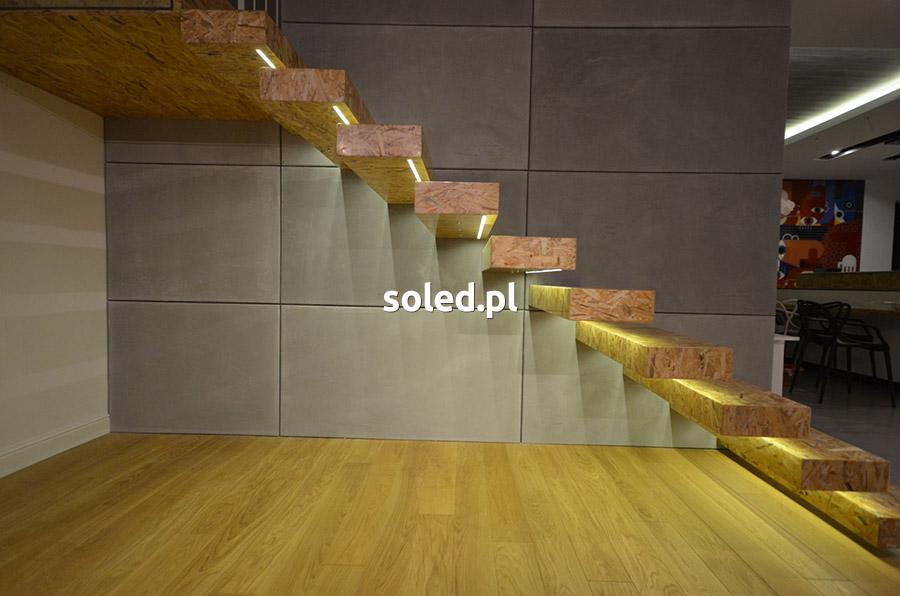 oświetlenie led schodów w domu, schody wykonane z płyty osb i wyglądają jakby wisiały w powietrzu, widok z boku schodów na ścianę