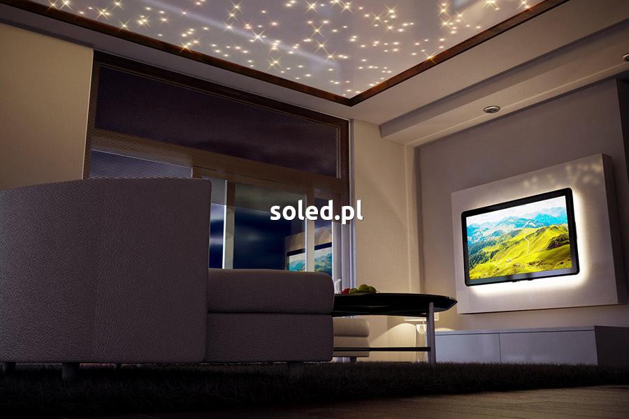 wizualizacja salonu widziana z perspektywy podłogi od strony kanapy, na środku stolik, na górze sufit napinany z gwiezdnym niebem, po prawej na ścianie telewizor włączony z krajobrazem, telewizor jest podświetlony taśmą LED