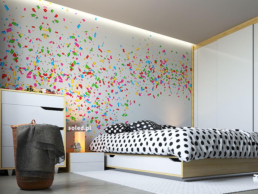 taśma LED biała zimna na suficie oświetla fototapetę abstrakcyjną w nowoczesnej jasnej sypialni, z prawej widzimy łóżko z pościelą z czarne kropki, obok łóżka znajduje się niska szafka nocna ze świeczką oraz komoda, meble biało-drewniane, najbliżej widza stoi koszyk w wiklinowym stylu z grafitowym kocem