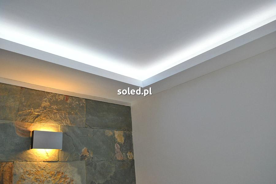 taśma LED do podświetlenia sufitu oświetla wnękę w salonie mieszkania nad ścianą z cegły